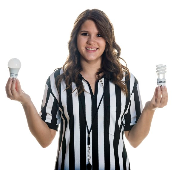 McKenzie Hanks in a referee shirt and whistle showing LED and CFL light bulbs for a story for Oklahoma LIving Magazine. This is the photo that I submitted with the story.