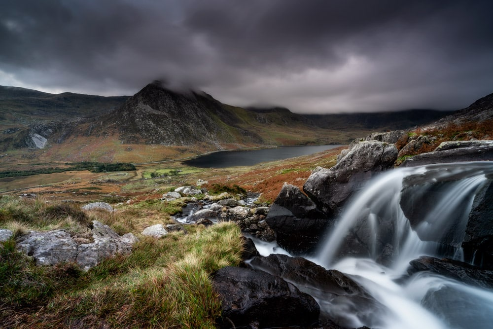 Afon Lloer with Tryfan and Llyn Ogwen in Snowdonia, North Wales on a moody evening.