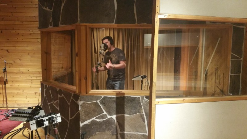 James Downham singing into a microphone in a recording studio.