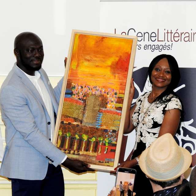 Elnathan John receives artwork from with Ngoãn Beti