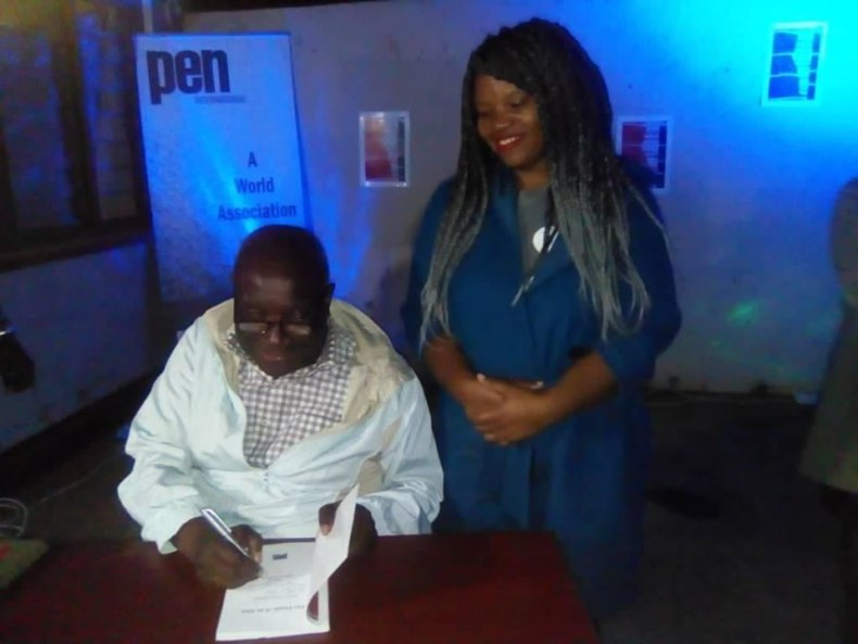 Pen Malawi President, Alfred Msadala, autographs a copy for first book auction winner Yamikani Chikoti