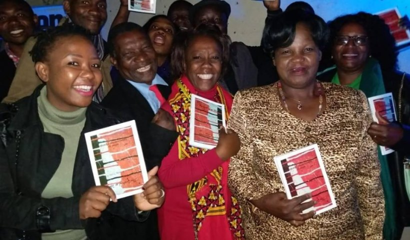 Anthology editor Egidio Hermes Mpanga, in red necktie and family including Hon Mary Mpanga, MP, in gold dress, who bought The Death of an idea auction copy at K50, 000