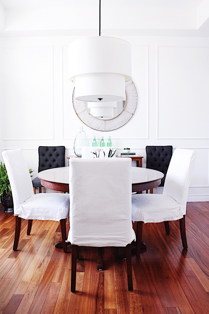 5 Tips to Declutter Your Home and Simplify Your Life-white and wood dining room with modern light fixture and picture frame wall molding