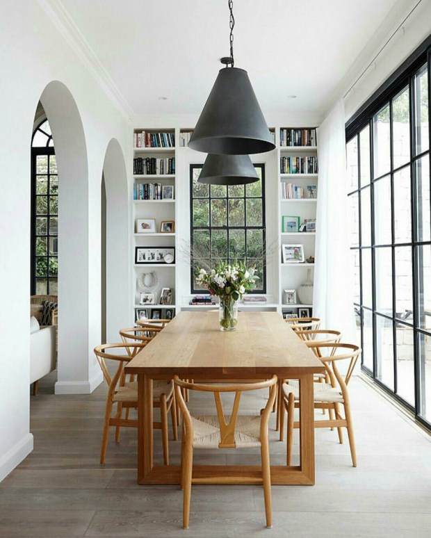 Beautiful dining room with wishbone chairs black light fixtures and black French doors / windows