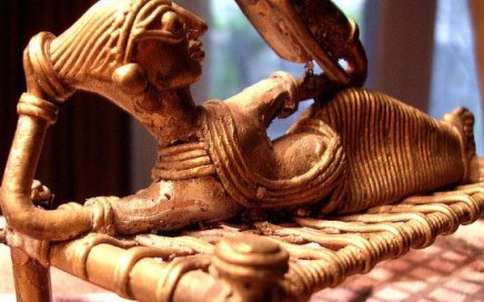 An image of a Central Indian tribal figuring of a woman reclining and reading a book.