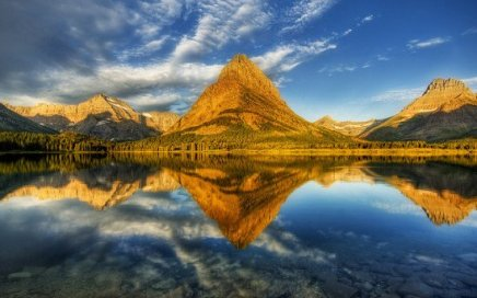 Mountains at the Glacier National Park reflected perfectly in a lake