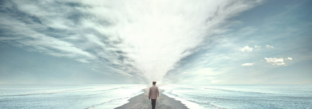 man walking on narrow beach with water on either side