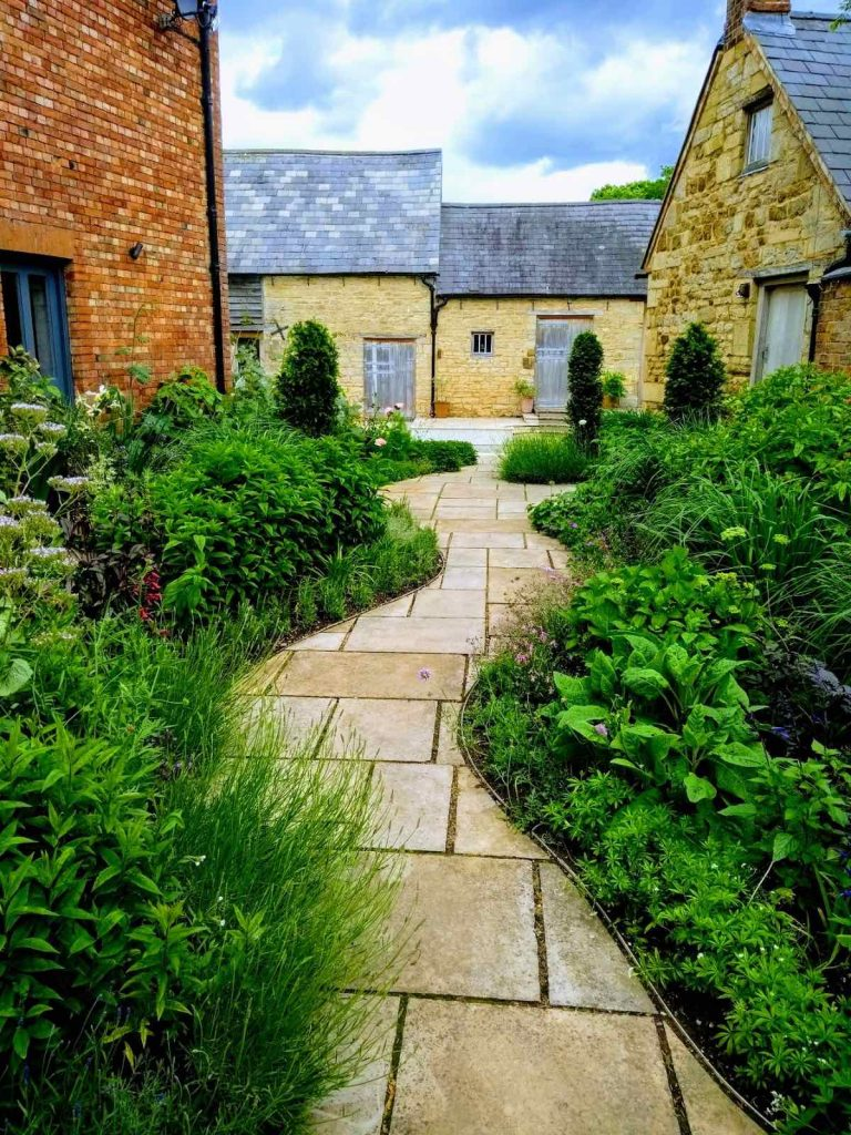 Wiggly stone path lined with green planting