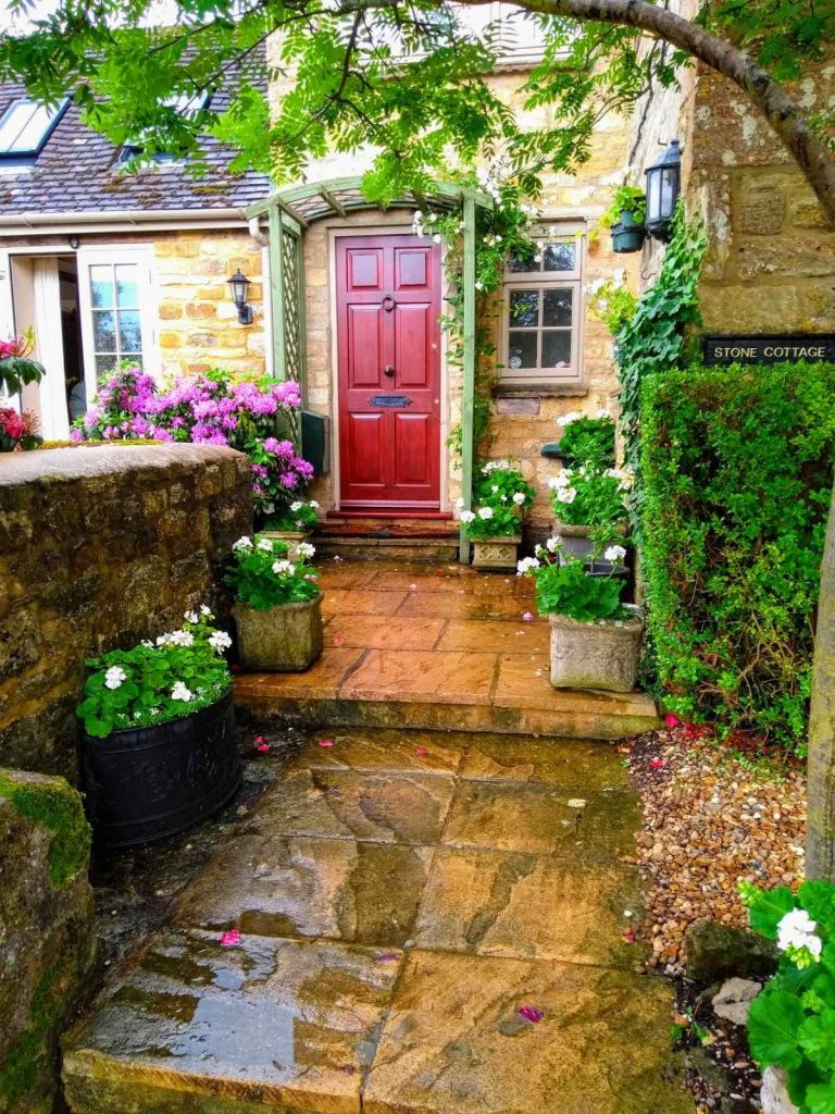 Stone paved path to red front door with pots of white pelargoniums