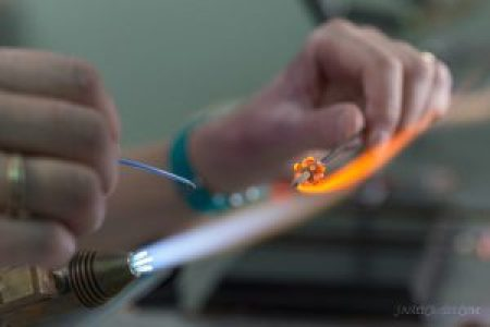 Melting glass to make glass beads - Janet Crosby