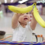 a 2 year old holding bananas sitting in the shopping cart