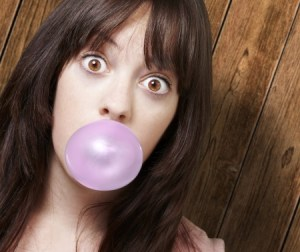 a young girl blowing a bubble with bubble gum