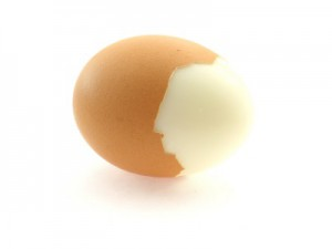A hard boiled brown egg half shelled.