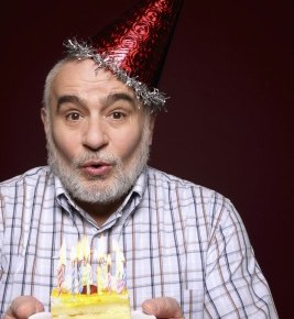 an older man with a birthday hat on blowing out candles on his birthday cake.