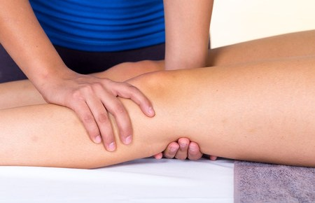 a young woman lying while getting a leg massage from specialist concept of physiotherapy.