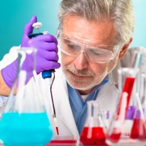 an older male researcher dropping fluid out of a beaker
