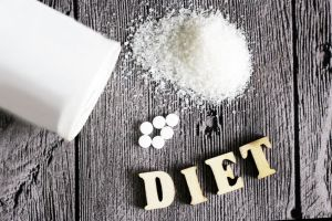 sweetener tablet and sugar. text diet wooden letters. food.