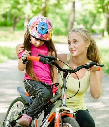 a mom talking to her daughter on her bicycle.
