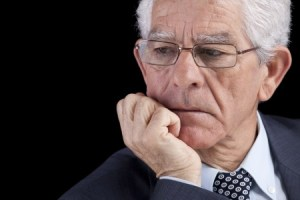 an older businessman with white hair leaning on his chin