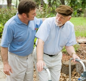 a young man walking with an older man using a walker