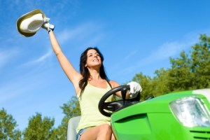 a young women waving her hat while driving a John Deere tractor
