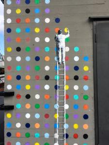 a main on a ladder painting colored dots on a wall