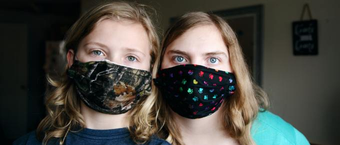 2 young girls wearing masks