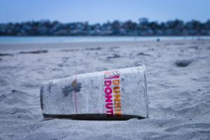 a plastic dunkin donut cup thrown on the beach