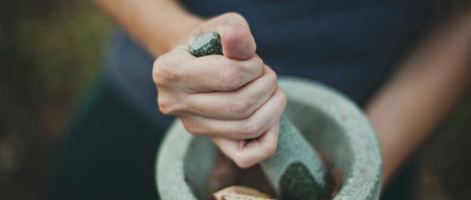 a woman crushing fresh herbs in a bowl