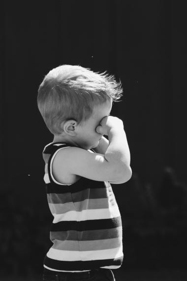 a little boy rubbing his eyes with allergies