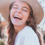 a laughing girl with a sun hat on