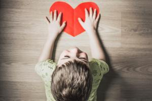 a small child with his hands on a drawn red heart