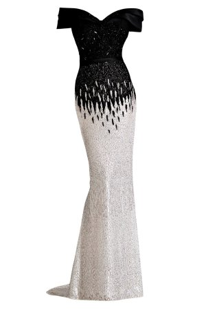 Off the shoulder gown with encrusted lace. Black and white long dress by Janique. Evening wear dress with beaded bodice.