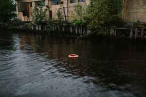 red boat on water near green trees