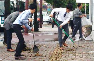 Des employés de bureau balayant des feuilles sur le trottoir de l'entreprise.
