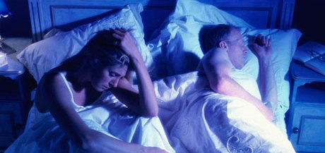A sleepless woman next to her partner in bed