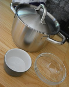 Kastrull med lock, värmetålig skål och något som skålen kan stå på inuti kastrullen.