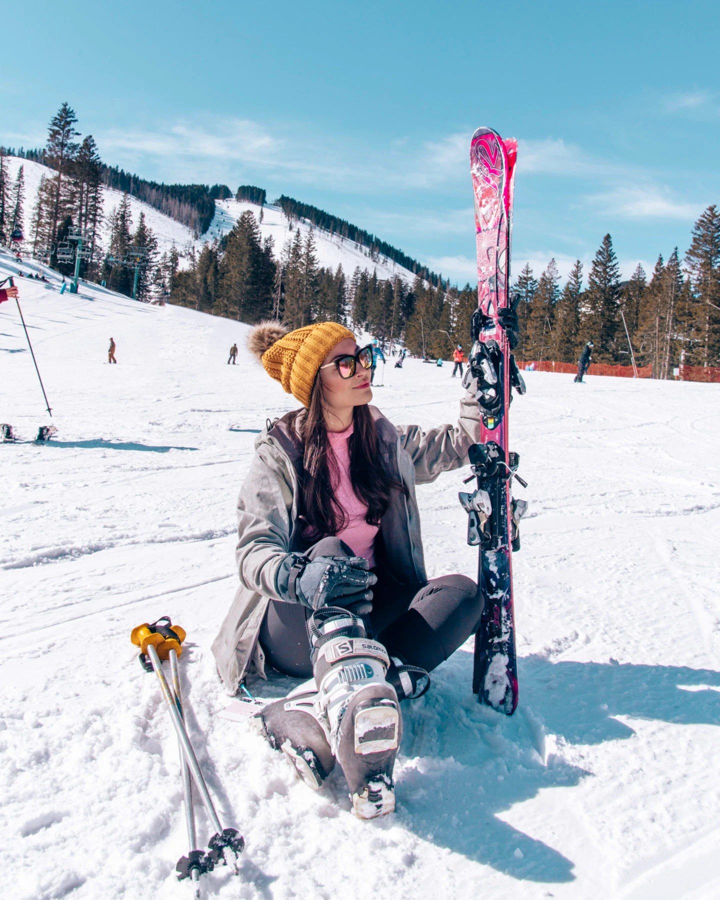girl sitting on snow holding skis