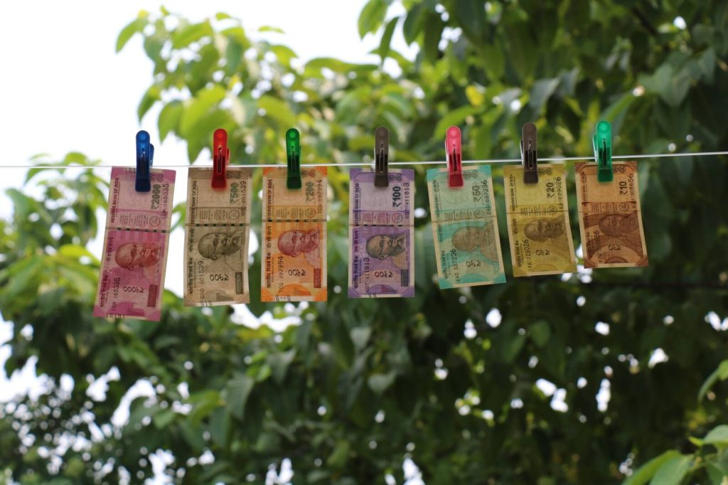 seven indian rupee banknotes hanging from clothesline on clothes pegs