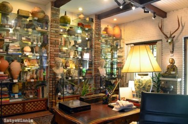 Etalasenya penuh dengan barang antik dan buku-buku sejarah.