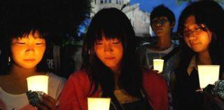 Foto: AFP. Jóvenes japoneses en el homenaje anual a las víctimas de la bomba atómica. Al fondo, el edificio del Domo (ドーム). Hiroshima (Japón)