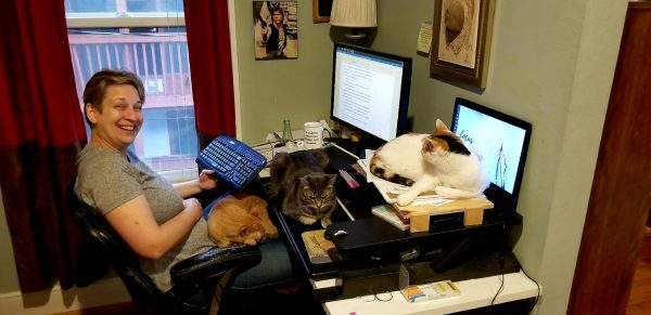 Jax siting at her desk with three cats all over her desk.