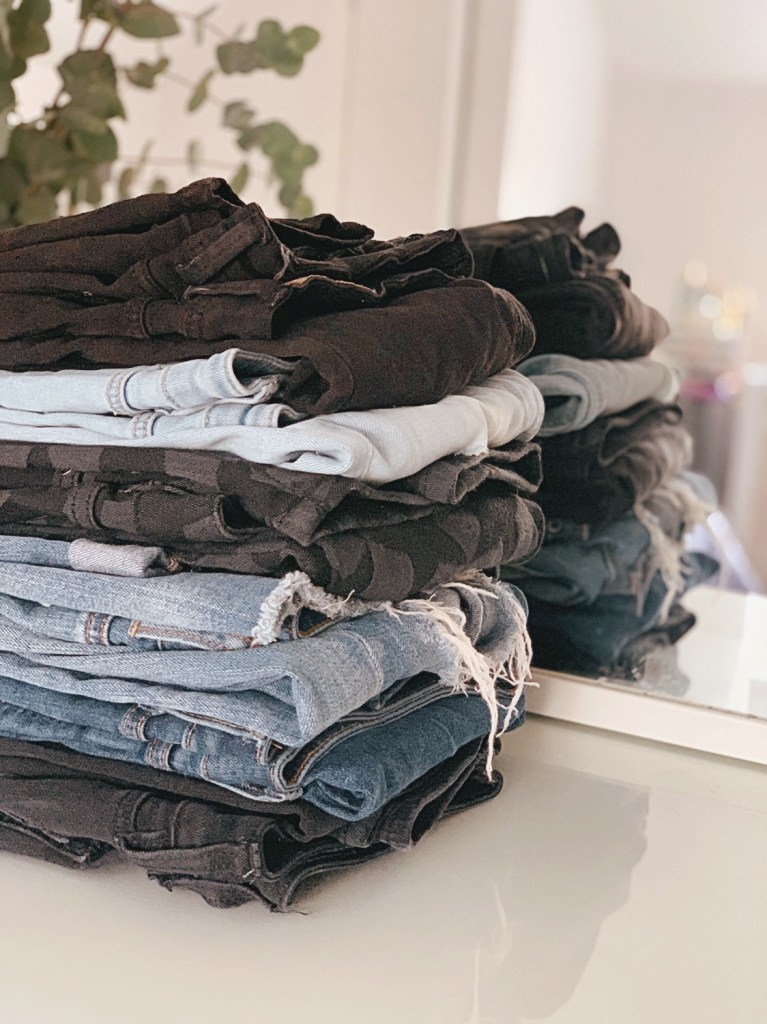 Jaye Rockett stack of jeans with mirror reflection