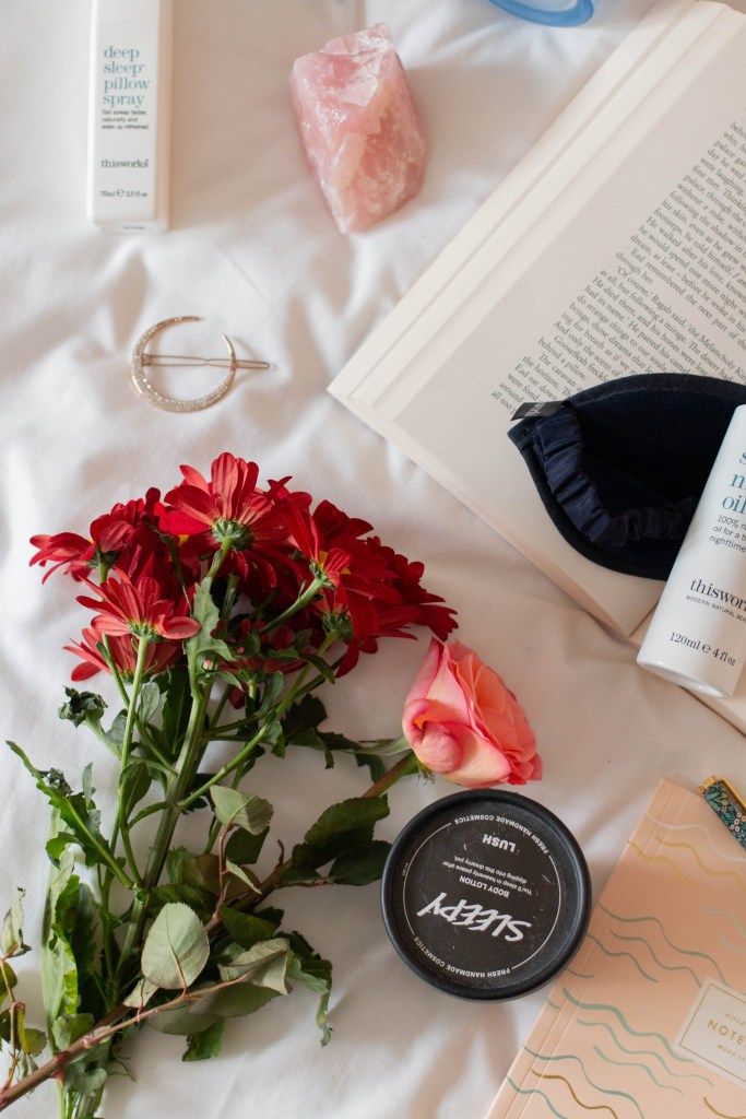 Flowers on bed, pot of Lush Sleepy body lotion, notebook.