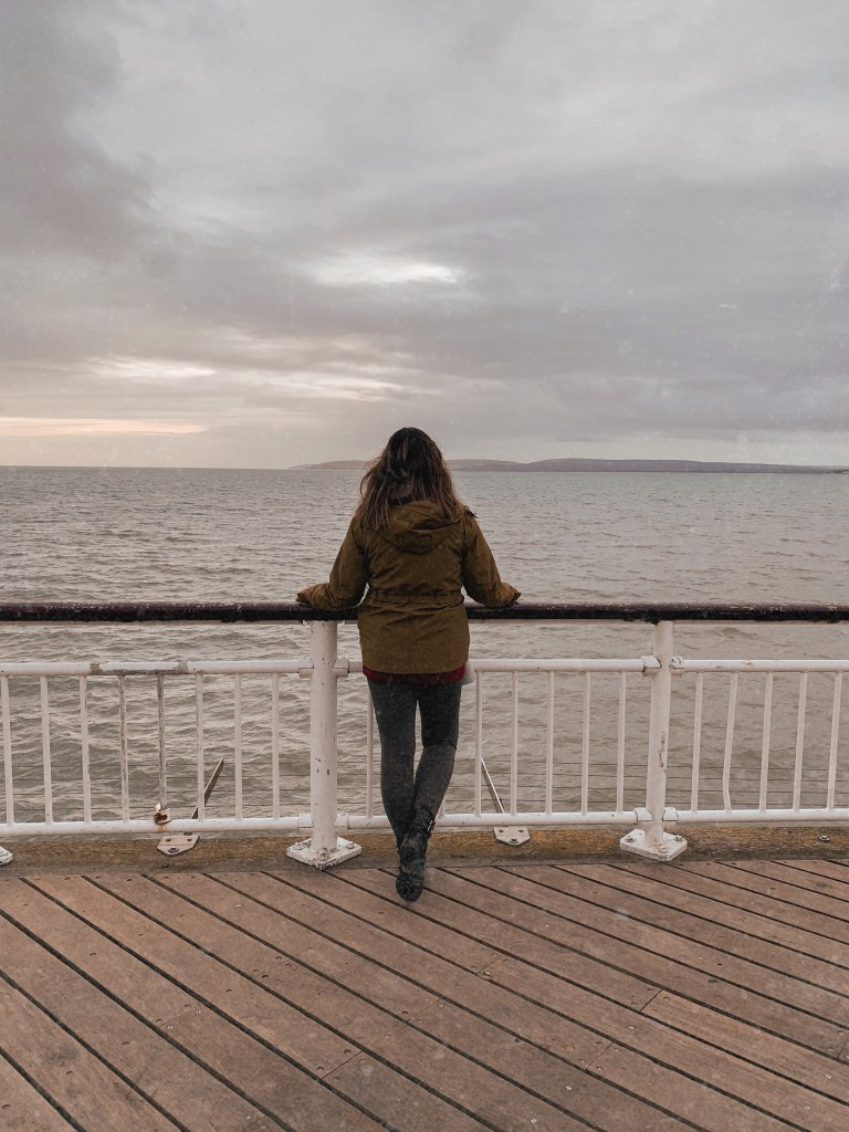 Jaye stands on a pier facing out to sea on a grey day.