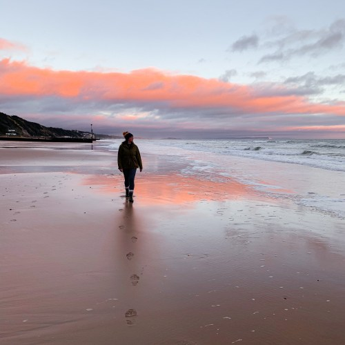 Jaye faces away from the camera stood on the beach at sunset, the skiy is pink and slightly cloudy, the tide is out so the wet sand reflects the sunset.