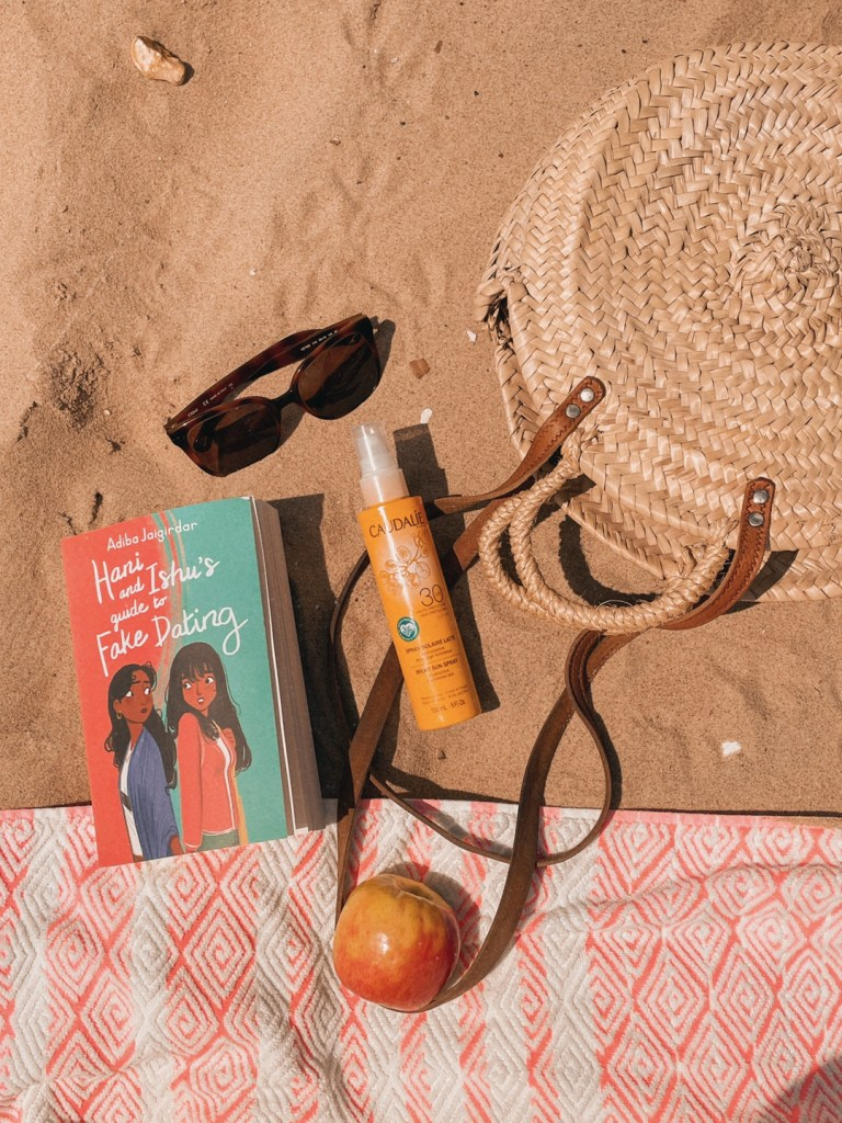 A flatlay on the beach featuring Hani and Ishu's Guide To Fake Dating, a wicker handbag, brown sunglasses, a bottle of suncream, an apple and a beach towel.
