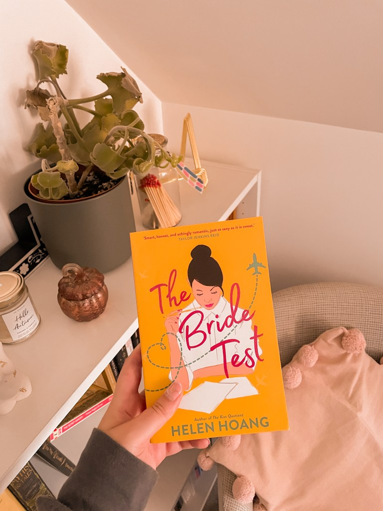 A photo of The Bride Test by Helen Hoang, with a bookcase in the background, and a chair with a pink cushion