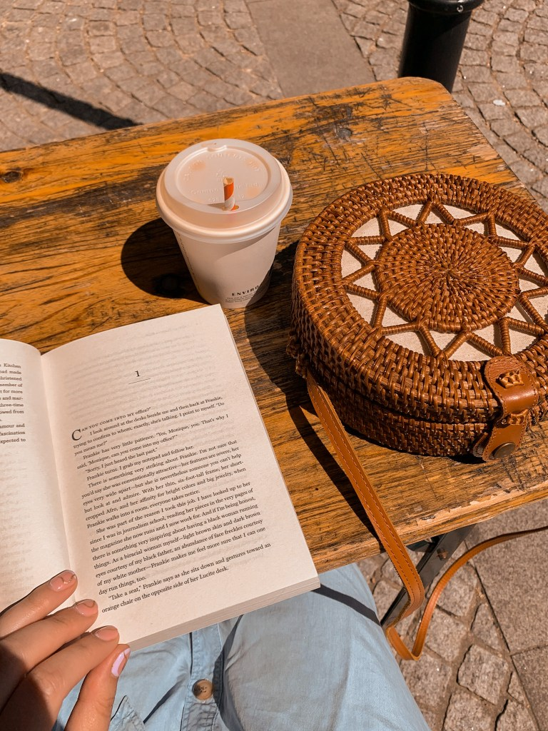 Flatlay of open book, iced coffee and brown wicker handbag open on wood table in the sunshine.