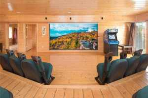 Home Theater Lodge is a massive eight bedroom cabin in Pigeon Forge with an amazing mountain view, huge theater room, arcade, and sleeps 34 people.